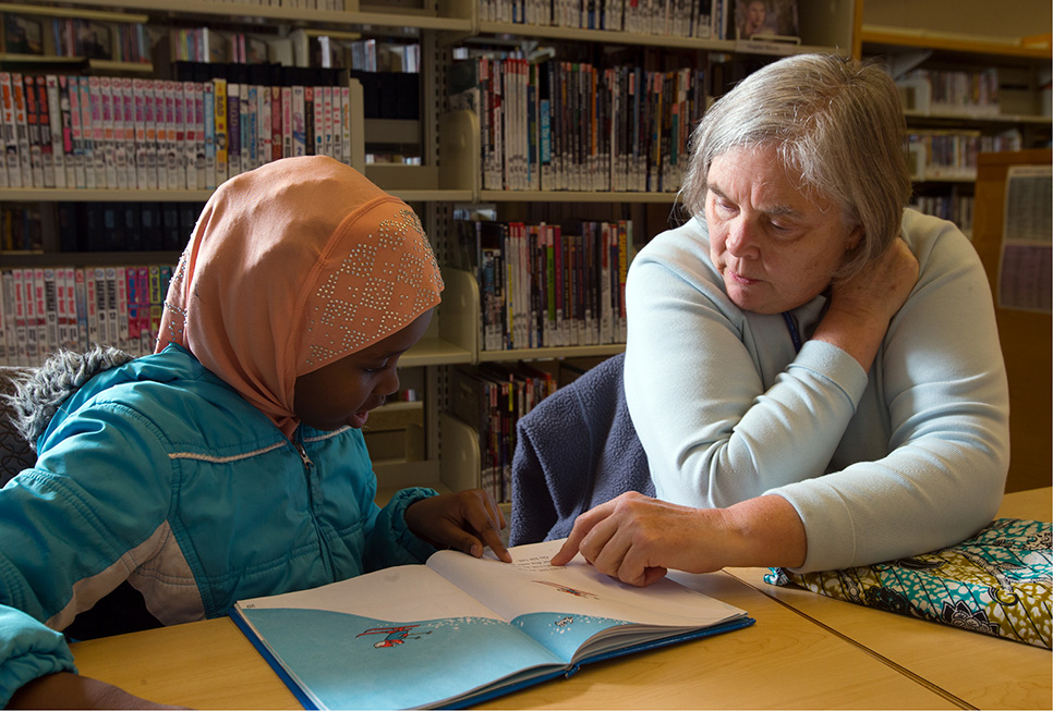 Teen patron receiving homework help from our Library volunteer at our Rainier Beach branch.
