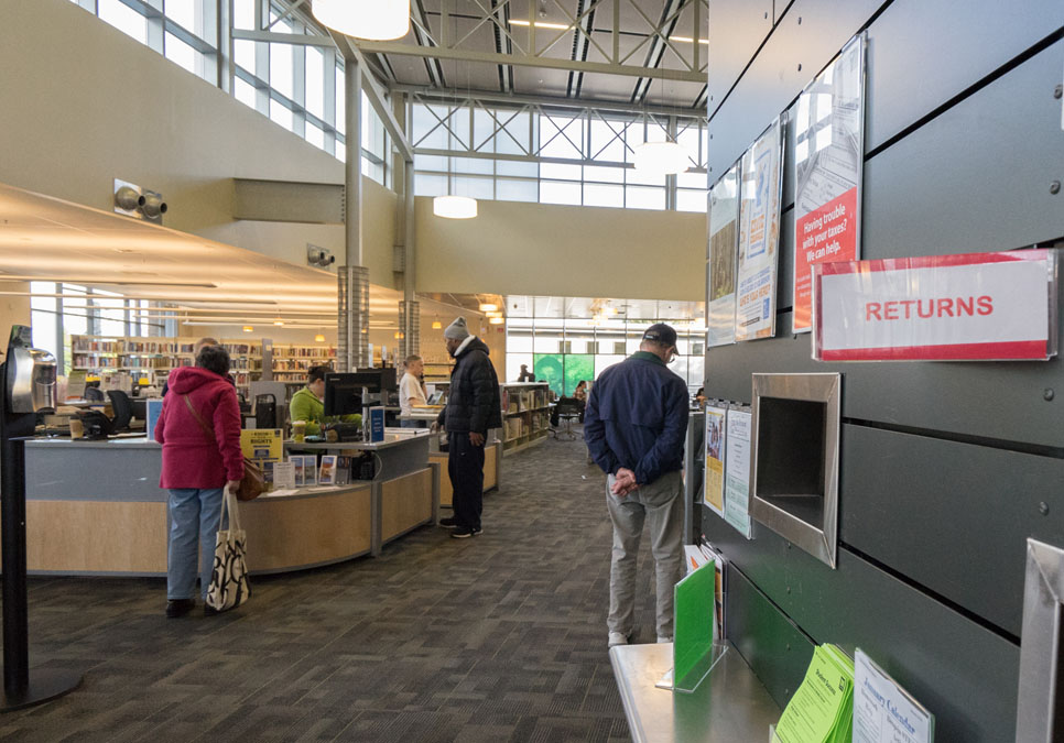 Library patrons at the service desk area at the Greenwood Branch